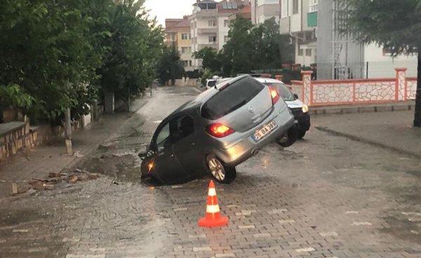 Otomobil, yağış nedeniyle çöken yola düştü